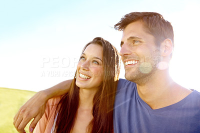 Buy stock photo A smiling couple looking upwards while standing outside