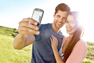 Buy stock photo A couple in a field posing for a picture of themselves with a cellphone