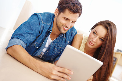 Buy stock photo Low angle shot of a young couple lying on their living room floor and using a digital tablet