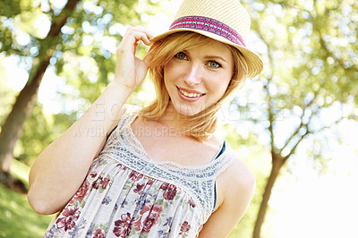 Buy stock photo Portrait of cute smiling blonde posing touching her hat in the park