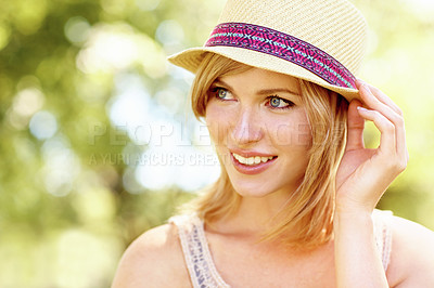 Buy stock photo Pretty blonde holding on to her hat and looking sideways outside
