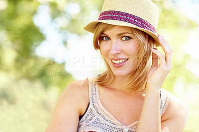 Buy stock photo Portrait of a cute blonde woman holding on to her hat with an outdoors background with copyspace