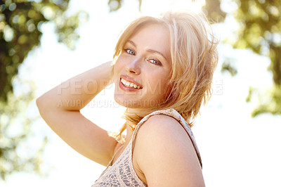 Buy stock photo Portrait of a beautiful young woman in a park smiling with the sun shining behind her