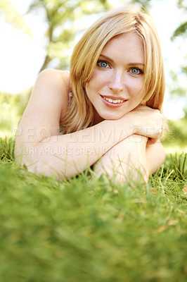 Buy stock photo Portrait of a beautiful young smiling woman lying on grass in an outdoor environment