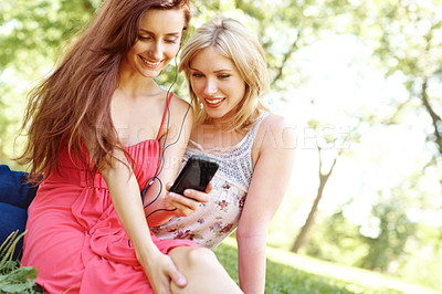 Buy stock photo Two beautiful friends sitting in a park and listening to music