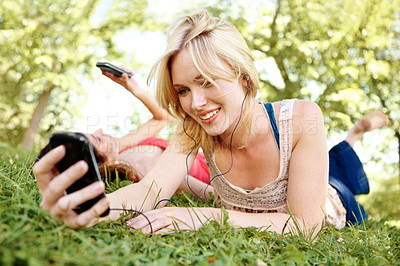 Buy stock photo A beautiful young woman lying on the grass and listening to music with her friend texting in the background