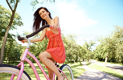 Buy stock photo A beautiful woman riding her bicycle