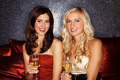 Buy stock photo Two beautiful women sitting in a nightclub drinking champagne
