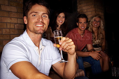Buy stock photo A handsome man holding a glass of champagene with friends sitting in the background