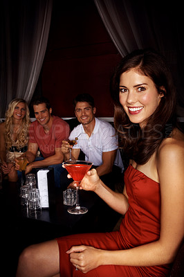 Buy stock photo A beautiful woman holding a cocktail with friends sitting in the background