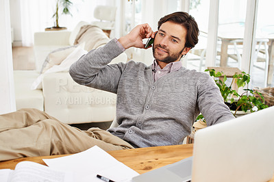 Buy stock photo A handsome businessman speaking on his mobile at his desk