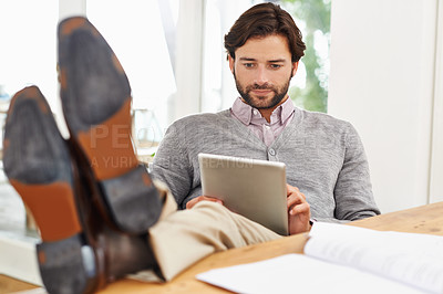 Buy stock photo A handsome businessman relaxing at his desk