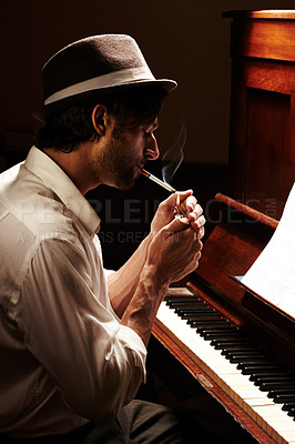 Buy stock photo Profile of a handsome man having a smoke at his piano