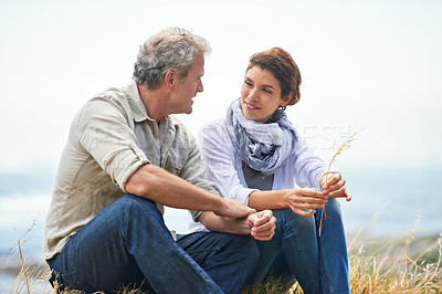 Buy stock photo Portrait of a mature couple sitting in the countryside