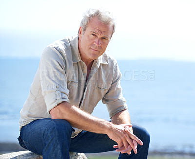 Buy stock photo Portrait of a rugged man sitting outdoors and looking at the camera
