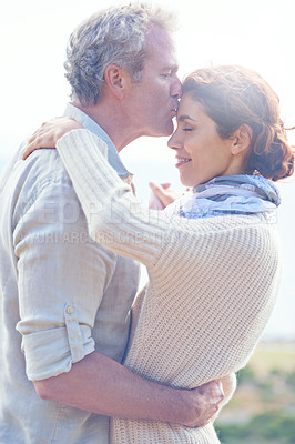 Buy stock photo Shot of a mature loving couple embracing one another and kissing