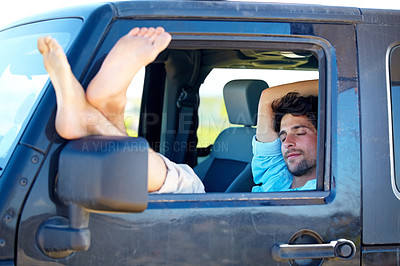 Buy stock photo A young man relaxing in his car with his feet out the window