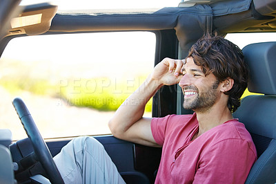 Buy stock photo A young man enjoying his vacation road trip with a smile
