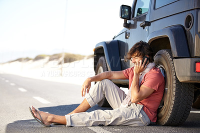 Buy stock photo A young man phoning for roadside assistance