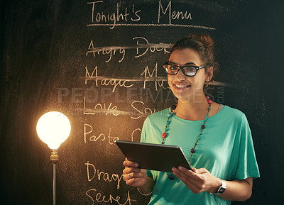 Buy stock photo Shot of a woman standing in front of a blackboard while holding her digital tablet