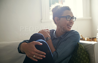 Buy stock photo Shot of a young woman relaxing on her sofa at home