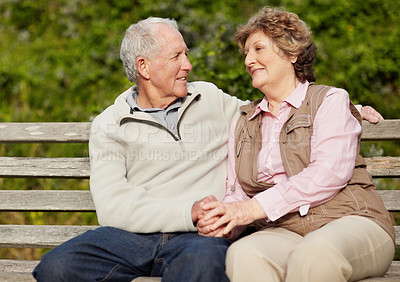 Buy stock photo Portrait of a romantic mature couple sitting on bench in countryside