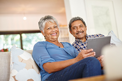 Buy stock photo Shot of a happy senior couple using a digital tablet together at home