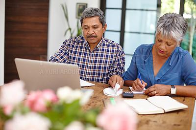 Buy stock photo Shot of a senior couple working on their budget together at home