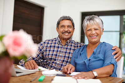 Buy stock photo Shot of a happy senior couple working on their budget together at home