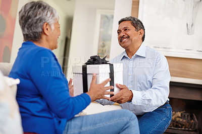 Buy stock photo Shot of a loving senior man surprising his wife with a gift