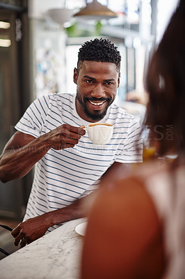 Buy stock photo A young man drinking a cup of coffee at a cafe counter