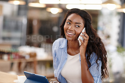 Buy stock photo Cropped shot of an attractive woman sitting in a coffee shop using a cellphone and tablet