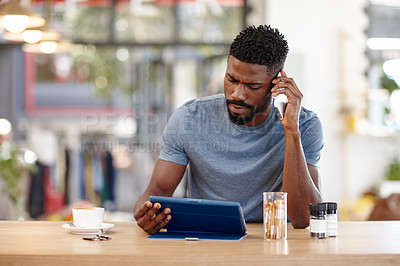 Buy stock photo Cropped shot of a handsome man sitting in a coffee shop using a cellphone and tablet