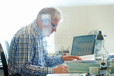 Buy stock photo Shot of a senior businessman going through paperwork at his desk while wearing a headset