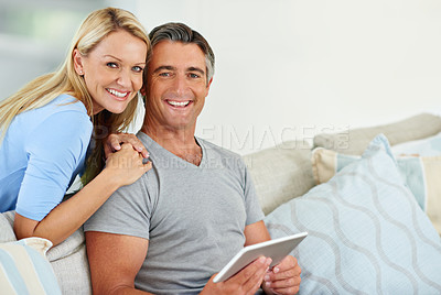 Buy stock photo Portrait of a mature couple sitting at home using a digital tablet