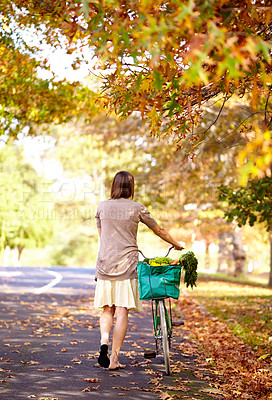 Buy stock photo Rearview shot of a young woman walking home from the grocery store with her bike