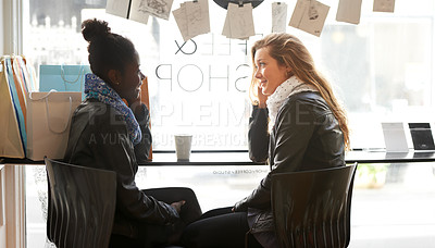 Buy stock photo Two young women buying coffee together