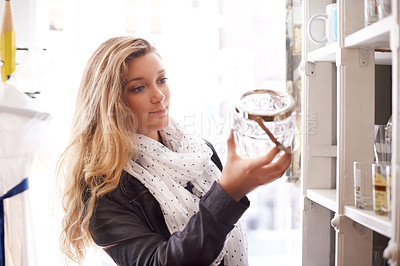 Buy stock photo A young woman holing a bottle in a shop