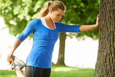 Buy stock photo A young woman stretching while leaning against a tree