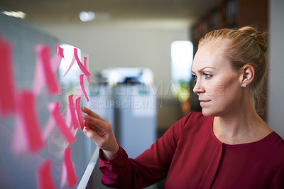 Buy stock photo Cropped shot of an attractive businesswoman checking the tasks on the sticky note board