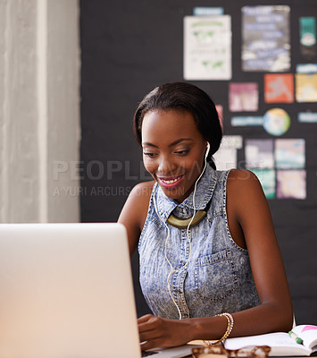 Buy stock photo Shot of a young designer listening to music while working on her laptop