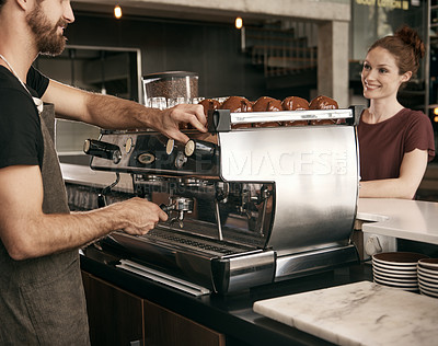 Buy stock photo Cropped shot of a male barista making a cup of coffee for a female customer