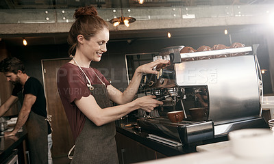 Buy stock photo Cropped shot of an attractive female barista making a cup of coffee