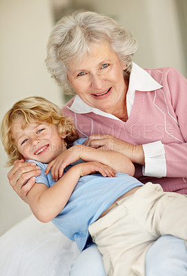 Buy stock photo Portrait of a playful child sitting on his grandmothers lap