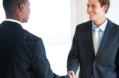 Buy stock photo Portrait of a happy young businessman shaking hands over a deal
