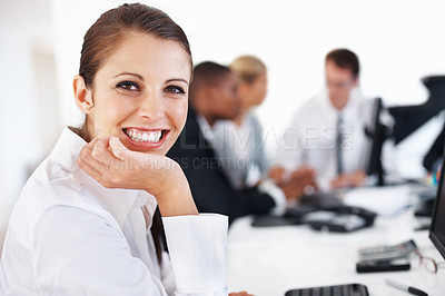 Buy stock photo Portrait of a happy young businesswoman smiling and her colleagues working behind at office