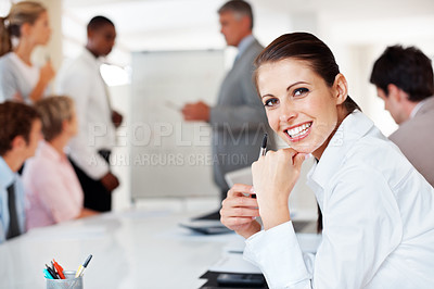 Buy stock photo Happy businesswoman sitting in office with colleagues working in background