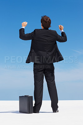 Business man in black suit with arms out against blue sky