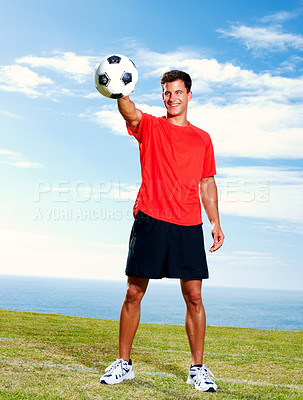 Happy male soccer player standing with a football