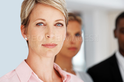 Buy stock photo Portrait of a smart young businesswoman looking confident with her colleagues standing behind